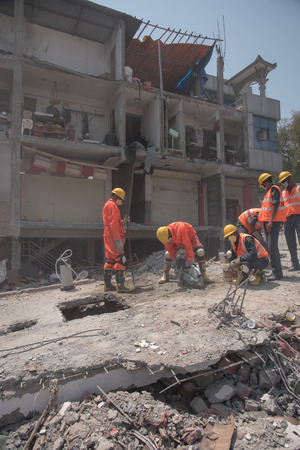 richter: KATHMANDU, NEPAL - MAY 1, 2015: soldiers with debris of buildings near Sobhavagbati bridge damaged after the major earthquake on 25 April 2015.