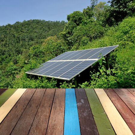 solar farm: Wood table top on solar farm background montage concept