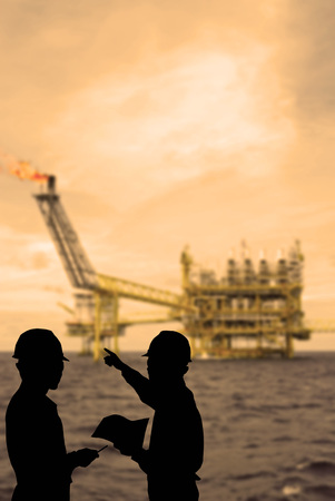 oilrig: Silhouette of engineers looking at rig in sepia tone Stock Photo