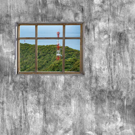 cement pole: windows frame on cement wall and view of seascape and communication pole