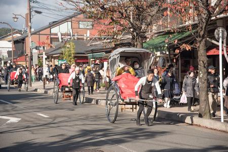 rikscha: KYOTO, JAPAN - NOVEMBER 26: Rickshaw in Kyoto, Japan on November 26, 2015. Unidentified man with a rickshaw and tourists near Tenryuji Temple