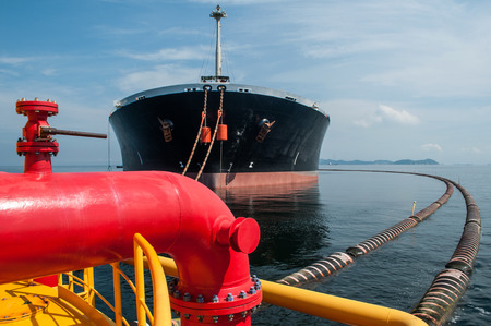 Oil tanker is transferring oil to the cargo vessel Stock Photo
