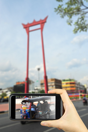 tuk: Giant swing and tuk tuk car, Suthat Temple, Bangkok, Thailand. Taking photo on smart phone concept.