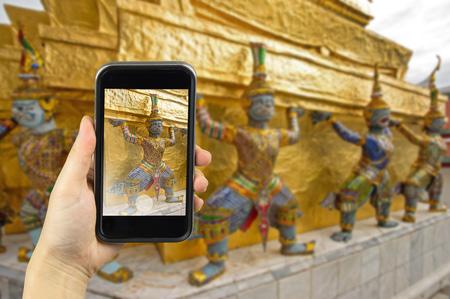brawny: Wat Phra Kaew royal palace, Bangkok, Thailand. Taking photo on smart phone concept.