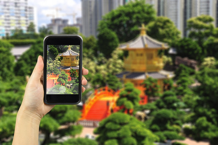 absolute: The Pavilion of Absolute Perfection in the Nan Lian Garden, Hong Kong. Taking photo on smart phone concept. Stock Photo