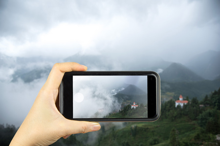 sa: take photo by smart phone concept. town of Sapa in green season view point from Hamrong Mt.