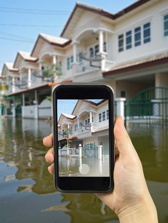 thailand flood: Taking photo on smart phone. Thailand flood crisis Stock Photo