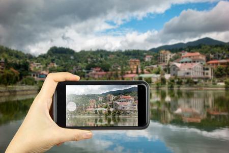 sa: Taking photo on smart phone. building along lake in sapa city, Lao cai, Vietnam