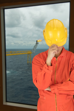 roughneck: Oil worker in orange uniform and helmet on of rig background Stock Photo