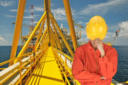 oil worker: Oil worker in orange uniform and helmet on of rig background Stock Photo
