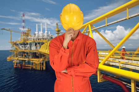 constrution site: Oil worker in orange uniform and helmet on of rig background Stock Photo