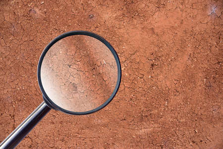 gauging: magnifying glass over crack wall