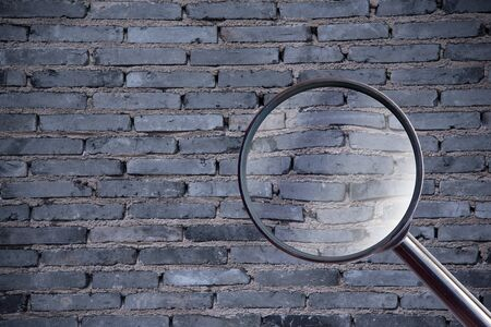 gauging: magnifying glass over brick wall