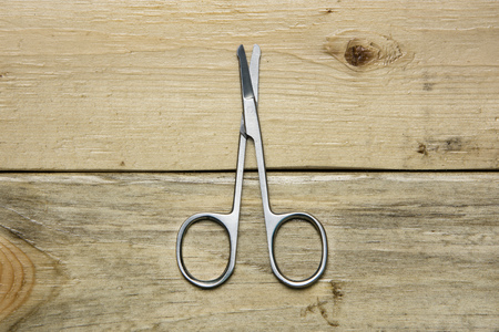 nail cutter: Scissors for trimming nose hair on wood background