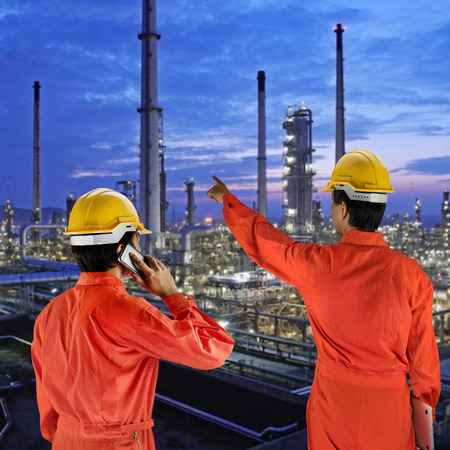 Oil workers in orange uniform and helmet on of rig background Stock Photo