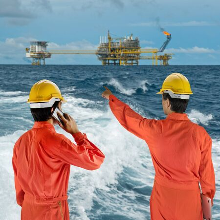 constrution site: Oil workers in orange uniform and helmet on of rig background Stock Photo