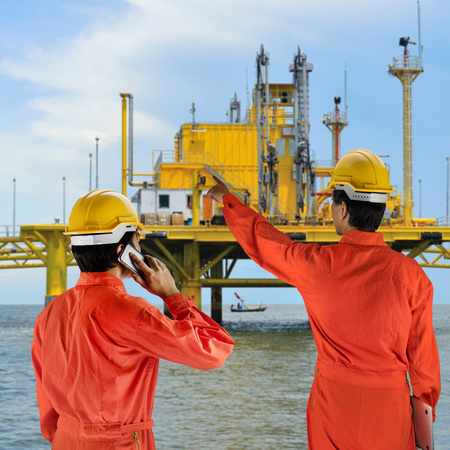 roughneck: Oil workers in orange uniform and helmet on of rig background Stock Photo