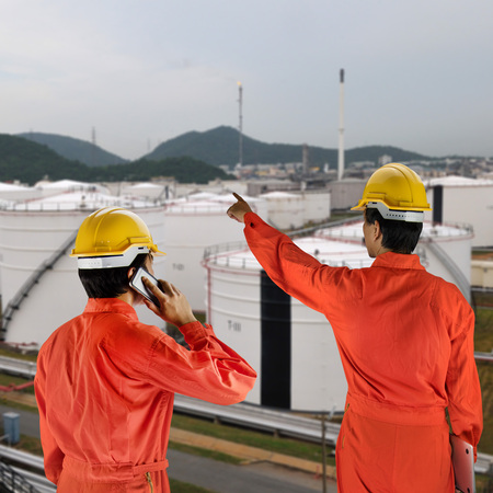 constrution site: Oil workers in orange uniform and helmet with oil tank Stock Photo