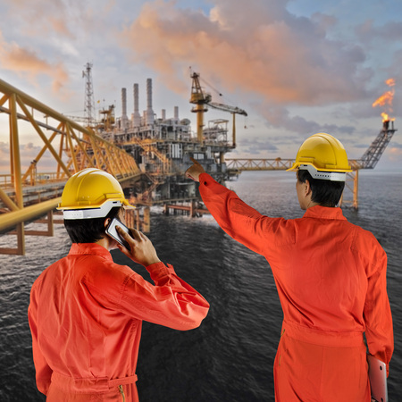 constrution site: Oil workers in orange uniform and helmet with rig background
