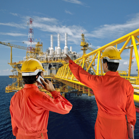 roughneck: Oil workers in orange uniform and helmet with rig background