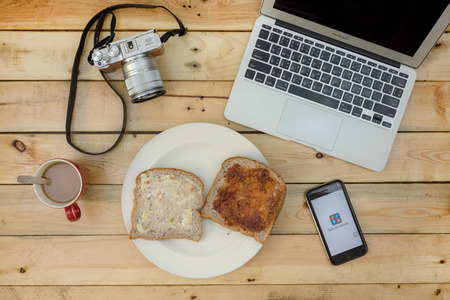 google plus: NAKORN PATHOM, THAILAND - FEB 18, 2016: laptop, camera, coffee, bread and screenshot of Google plus app on iPhone6 on wooden table. on wooden table. Editorial