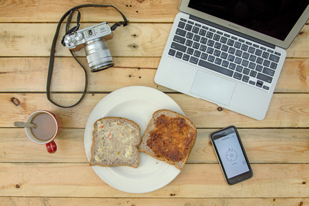 screenshot: NAKORN PATHOM, THAILAND - FEB 18, 2016: laptop, camera, coffee, bread and screenshot of fine my iPhone app on iPhone6 on wooden table. on wooden table.