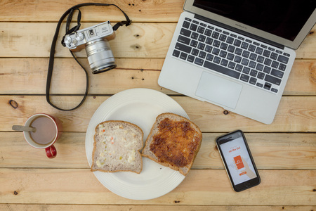 alibaba: NAKORN PATHOM, THAILAND - FEB 18, 2016: laptop, camera, coffee, bread and screenshot of Alibaba app on iPhone6 on wooden table. on wooden table. Editorial