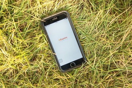 alibaba: NAKORN PATHOM, THAILAND - FEB 15, 2016: top view screen shot of Aliexpress apps showing on iPhone6 on grass