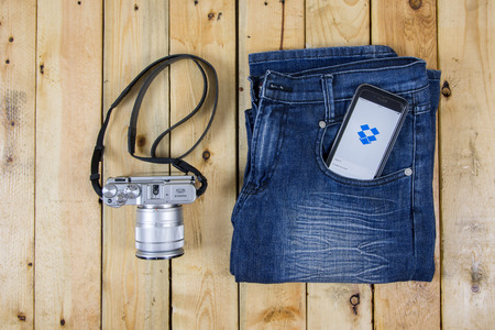 dropbox: NAKORN PATHOM, THAILAND - MAR 3, 2016: Dropbox app showing on iPhone 6 in pocket jean and Fujifilm camera on wooden table.