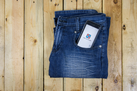 google plus: NAKORN PATHOM, THAILAND - MAR 3, 2016:  Google plus app showing on iPhone 6 in pocket jean on wooden table.