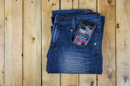 pinterest: NAKORN PATHOM, THAILAND - MAR 3, 2016: Pinterest app showing on iPhone 6 in pocket jean on wooden table.