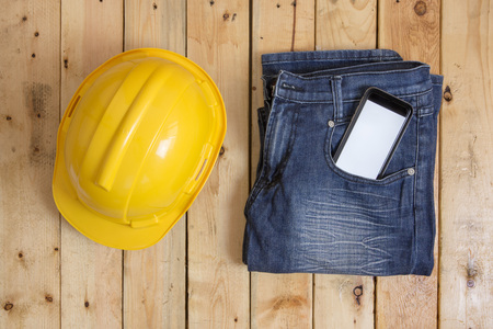 safty: smartphone, safty helmet and jean on wood plank from above