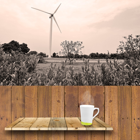 shelve: coffee cup on wood shelve and wood plank with wind turbine background