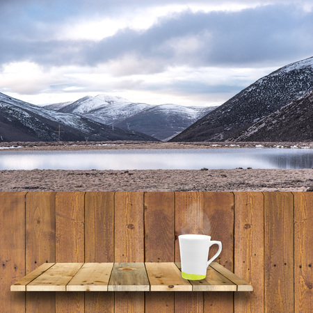 shelve: coffee cup on wood shelve and wood plank with snow mountain background