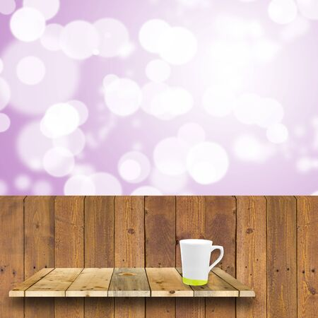 shelve: wood shelve hang on wood plank wiht coffee cup in front of bright bokeh lights Stock Photo