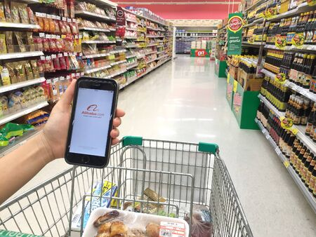 alibaba: NAKORN PATHOM, THAILAND - MAR 20, 2016: A woman hand holding screen shot of Alibaba app showing on iPhone 6 in Tesco Lotus supermarket.