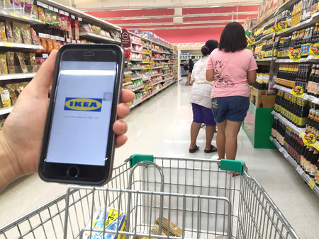 screen shot: NAKORN PATHOM, THAILAND - MAR 20, 2016: A woman hand holding screen shot of Ikea app showing on iPhone 6 in Tesco Lotus supermarket.