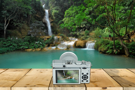 nature photo: camera with screen display on wooden table with beautiful landscape in the background