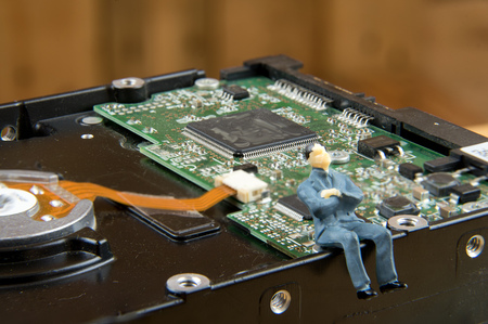 diskdrive: Miniature businessman on top of diskdrive. miniature photo concept Stock Photo