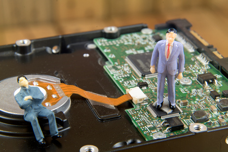 diskdrive: Miniature businessman on top of diskdrive. miniature photo concept Stock Photo