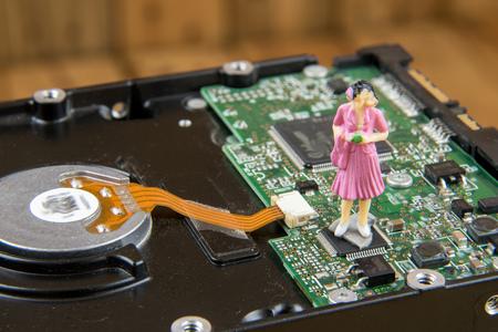 diskdrive: Miniature woman on top of diskdrive. miniature photo concept