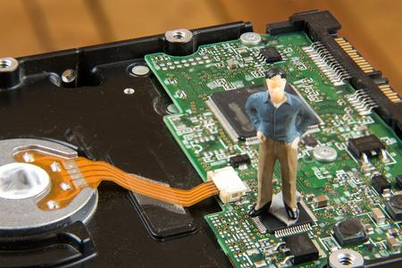 diskdrive: Miniature man on top of diskdrive. miniature photo concept