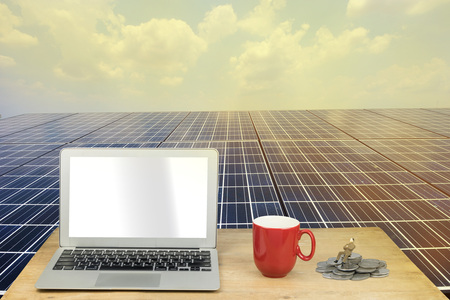 panel: laptop, red mug and miniature figure on wood table with solar panel