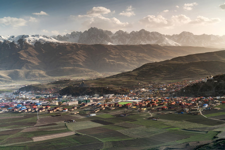 high priest: Village inclose mountain a famous landmark from view point from Long Youth Cole temple Ganzi, Sichuan, China Stock Photo