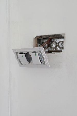 sockets: electric sockets installation in white walls at house construction site