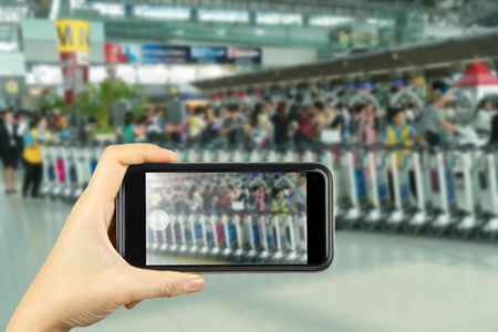 suvarnabhumi: hand hold smartphone with blurred of Suvarnabhumi Airport, Thailand Stock Photo