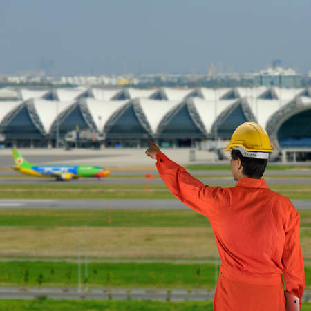 airstrip: engineer with helmet for workers security on background of architecture detail of Bangkok Airport in Thailand
