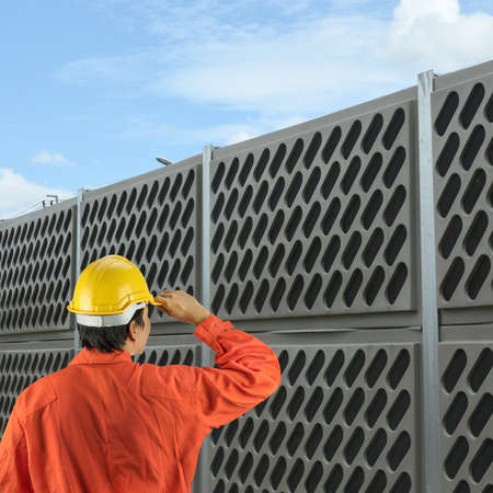 barrier: engineer with helmet for workers security on background of noise protective barrier