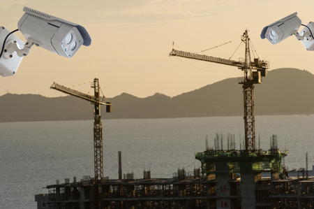 nightvision: cctv camera isolated on white background with construction site blur background Stock Photo