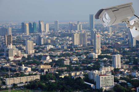 nightvision: cctv camera isolated on white background with modern building blur background
